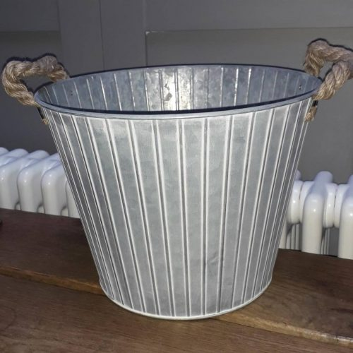 A metal bucket with a vertical ribbed design. It is tapered towards the base and has 2 rope handles