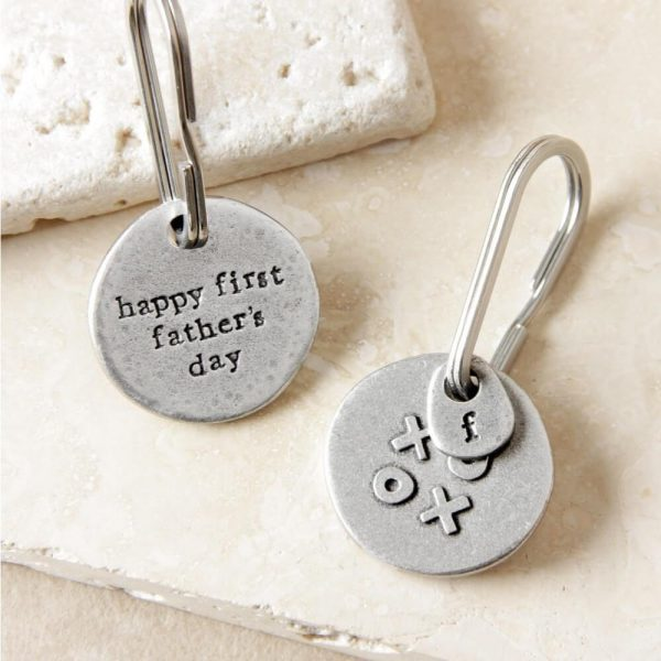 """Round metal keyring with X and o on one side and """"happy first father's day"""" inscribed on the other"""