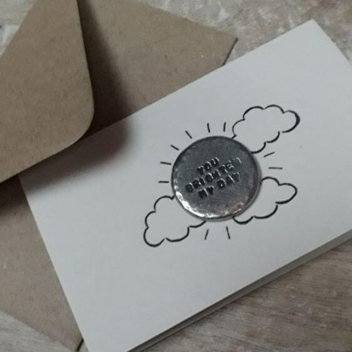 Silver token within cloud picture on card with envelope