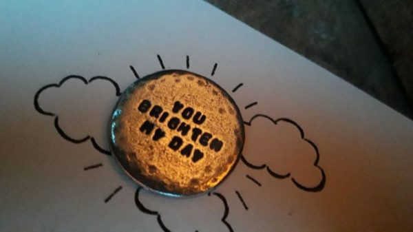 """Round metal token with the words """"You brighten my day"""" inscribed on it. The token is say on a plain white card with clouds drawn around it and sun rays drawn from the token"""