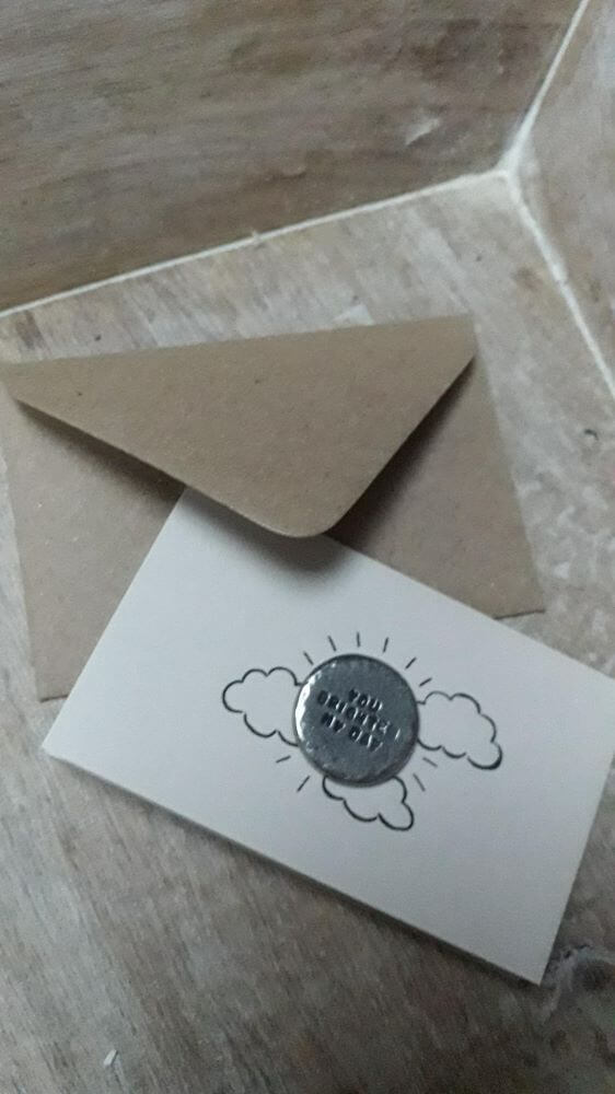 Token displayed with the card and envelope it accompanies