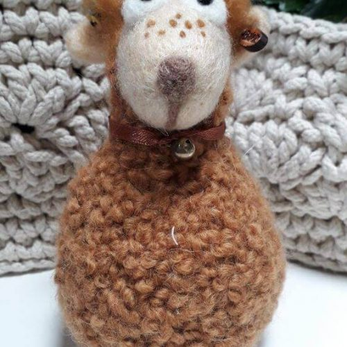 A brown sheep with a collar and bell around its neck