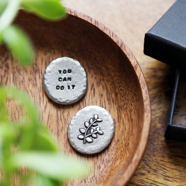 """Round metal token with a leaves imprinted on one side and the workding """"you can do it"""" on the other"""