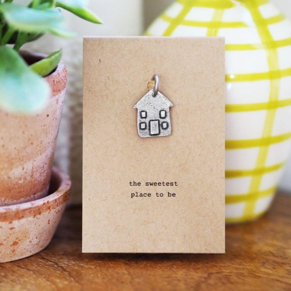 """Home sweet home token attached to a card with the words """"the sweetest place to be"""" printed on it"""