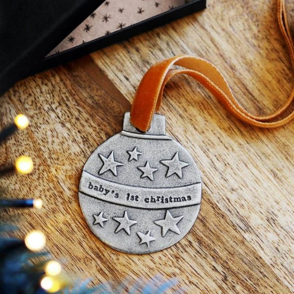 """metal round bauble with stars on and the band across the middle """"baby's 1st christmas"""" with a ribbon attached for hanging"""