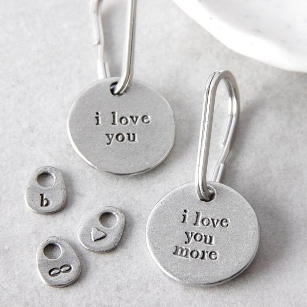 """tow keyrings with """"i love you"""" and """"il love you more"""" inscribed on them"""