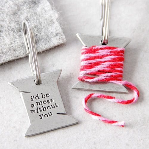 """Keyring bound with pink and red thread which when unraveled reveal the words """"I'd be a mess without you"""""""