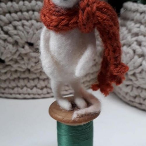 A white mouse standing on a bobbin with green thread. The white mouse has a hat on and brown knitted scarf around its neck
