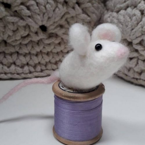 A white sugar mouse sitting on a bobbin with purple thread