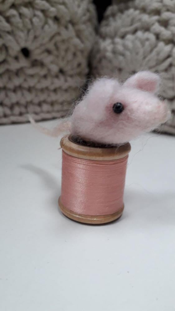 A pale pink sugar mouse sitting on a bobbin with pink thread