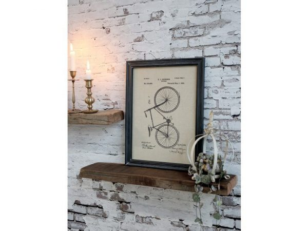 Framed picture of a bike displayed on a shelf