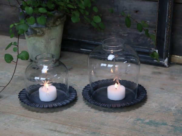 two candle holders. two different sizes displaying candles