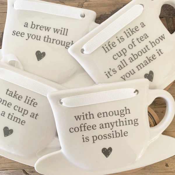 cup shaped ceramic ornaments with ribbon around the top and messages printed on