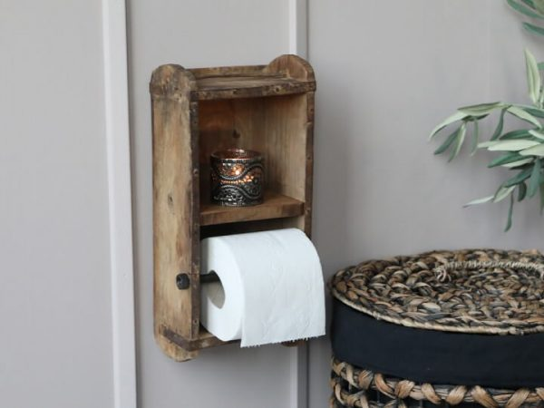 Wooden open box with a shelf at the top and a metal rod nearer the bottow to hold toilet roll
