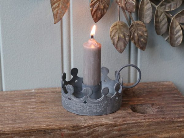 Grey metal crown design candle holder displaying a lit candle