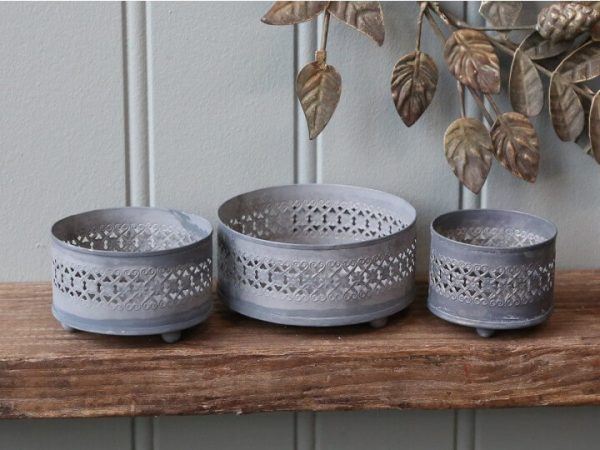 3 matching candle holders of different sizes. Round wiih a symmetrical patterned cut out design