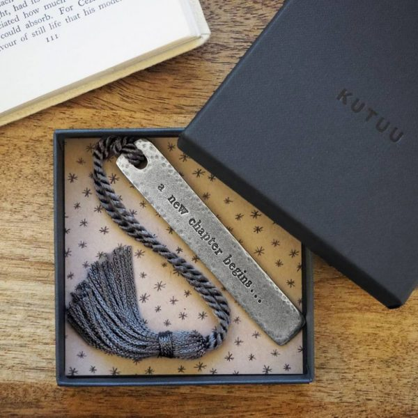 """Long metal bookmark with """"a new chapter begins,,,"""" enscribed on it with a hole at the top with a tassle tied through. Displayed in a presentation box."""