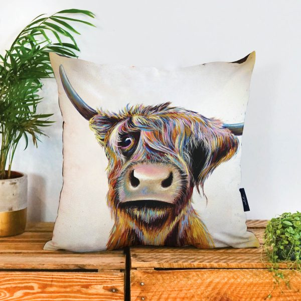 Face of a cow on a cushion looking forward on a neutral background. It has one horn pointing upwards and one to the side. It has a big nose and one eye is covered by its hair.