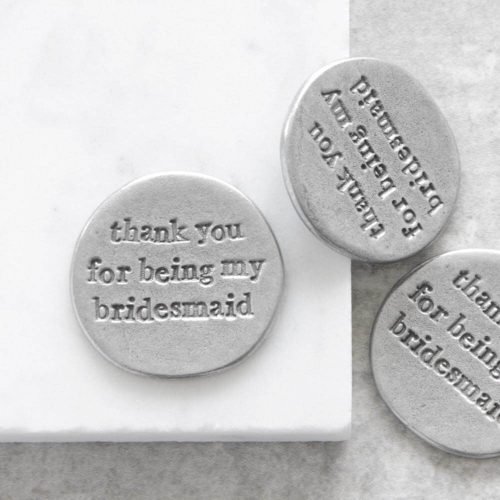 """Round metal token with """"thank you for being my bridesmaid"""" engraved within it."""
