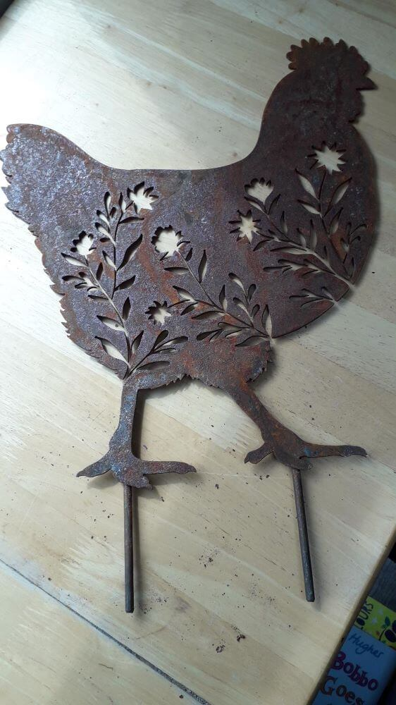 Rust chicken with flowers cut in to its body. Chicken is on 2 stakes to stand in ground