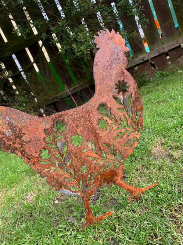 freestanding rusted cut out chicken. The cut outs are flower designs