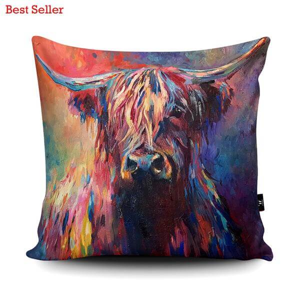 Picture of a cow facing foreward. Cushion is fully of colour. One eye of the cow is covered by its hair.