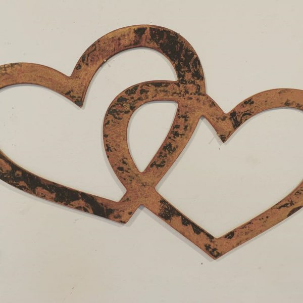 2 rusted cut out intertwined hollow hearts