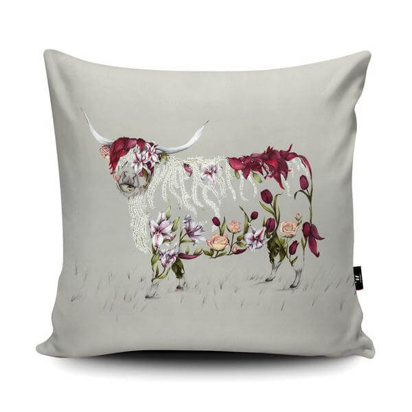 White coloured background cushion with a cow on. The cow is made up of flowers.