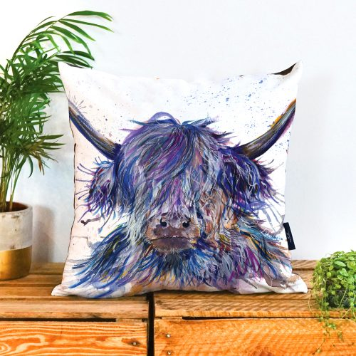 White background cushion with the face of a purple/blue coloured shaggy cow on it facing forward. The eys are covered by the long hair and it has big horns.