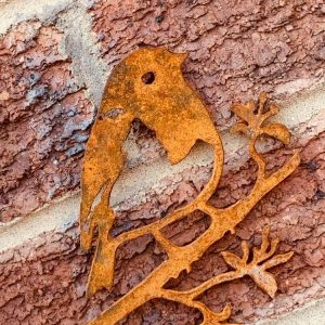 Rusted cut out robin standing on a branch