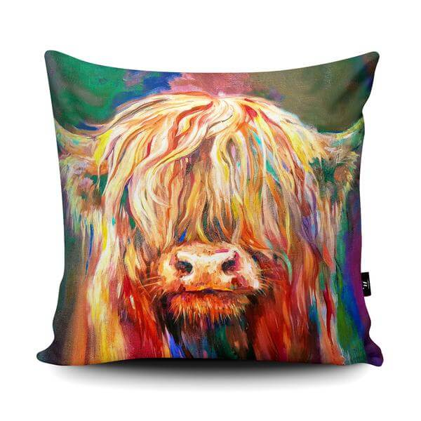 Cushion with a cow's face on facing forward. The cows eyes are covered by its long hair so only its nose is visible.