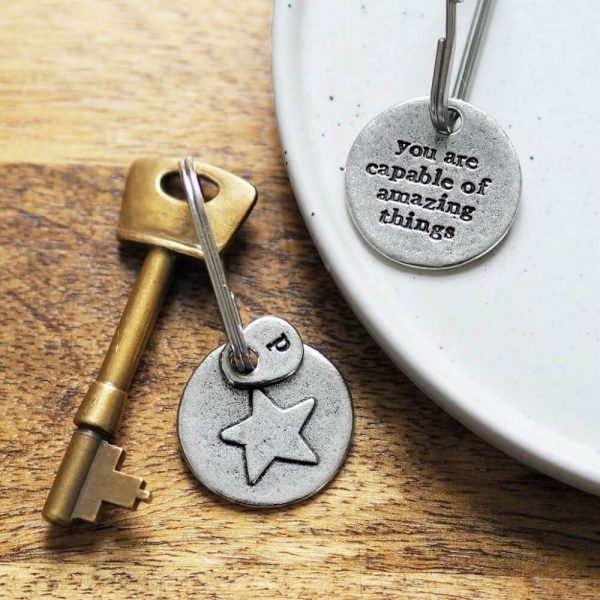 """Keyring with key attached. One side of keyring has a star design on ones side and """"your are capable of amazing things"""" engraved on other side"""