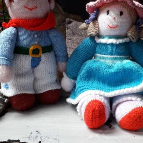 Knitted dolls. Boy has trousers, scalf, belt and hat. Girl has a knitted dress on a bonnet knitted hat and knitted hair bunches with ribbons in