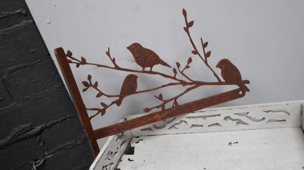 Rusty hanging basket bracket with a rusty branch and some rusty birds sitting on it